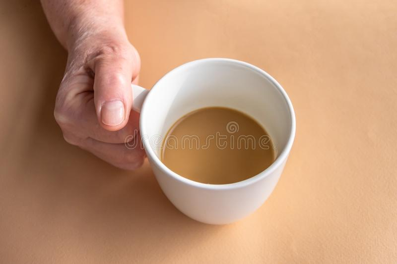 Elderly woman holds morning coffee with milk in hand.  stock photography