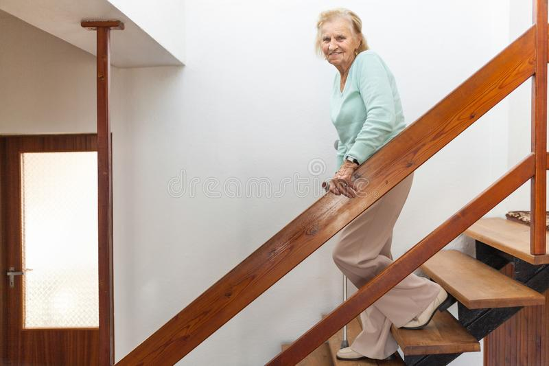 Elderly woman at home using a cane to get down the stairs stock image