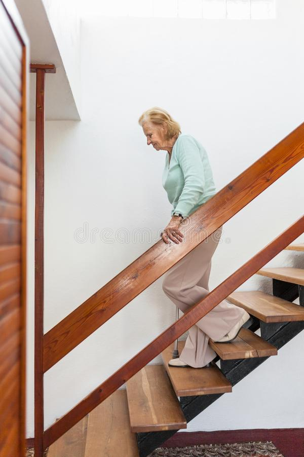 Elderly woman at home using a cane to get down the stairs royalty free stock photography