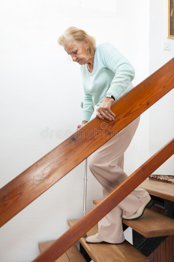 Elderly woman at home using a cane to get down the stairs stock photography