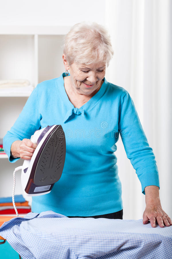 Elderly woman ironing stock images