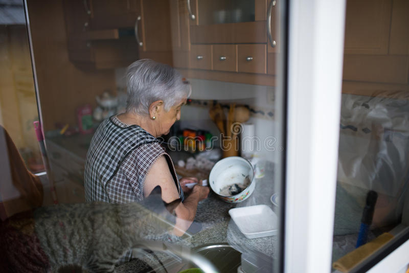 Elderly woman in the kitchen stock photo