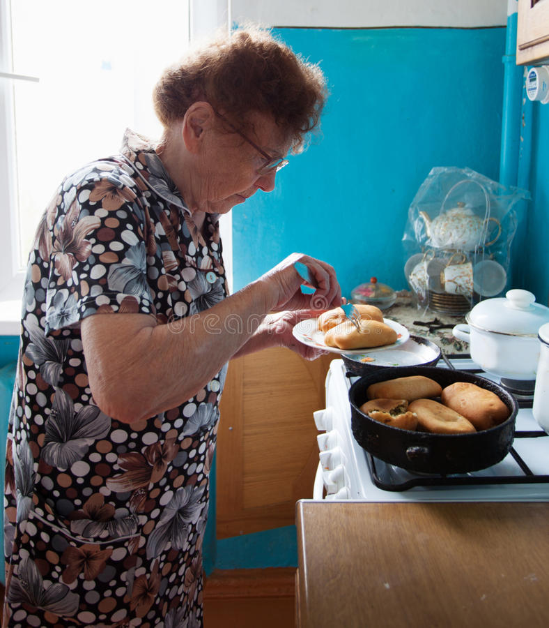 Elderly woman on the kitchen royalty free stock images