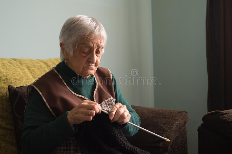 Elderly woman knitting at home. stock image