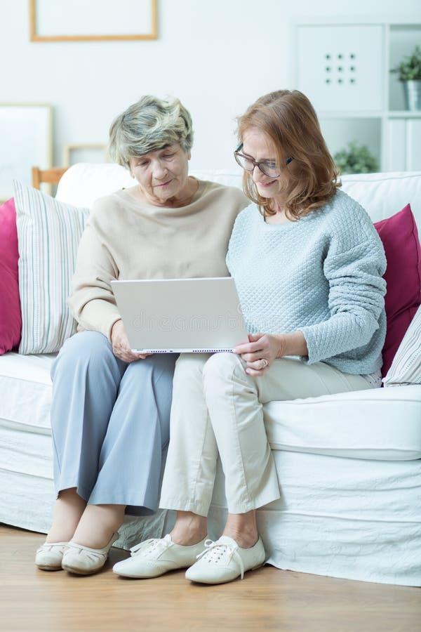 Elderly woman leraning computer skills. Portrait of elderly women learning computer skills with friend royalty free stock photo