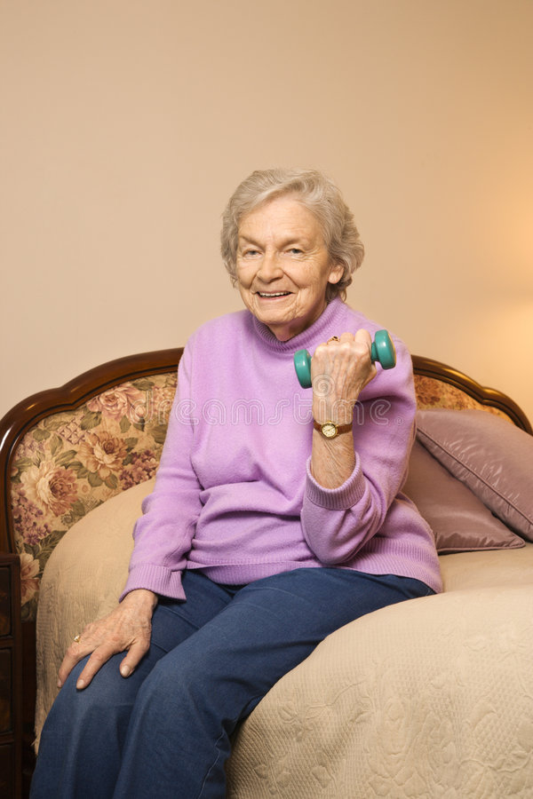 Elderly woman lifting weights. royalty free stock image