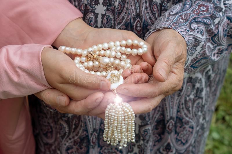 An elderly woman and a little girl are holding a beautiful white rosary. Hands of an old woman and a little girl with pearl rosary royalty free stock photography