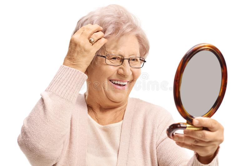 Elderly woman looking at herself in a mirror and making her hair stock photos