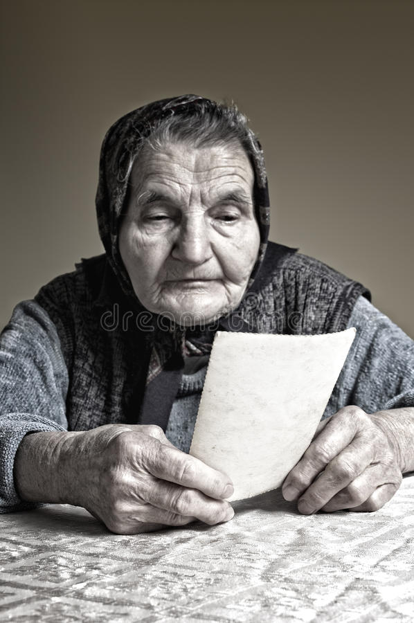 Elderly woman with old photos stock photo