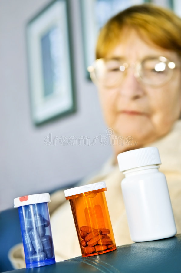 Elderly woman looking at pill bottles royalty free stock images