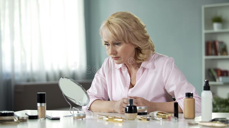 Elderly woman looking sadly in mirror with make-up on table, aging process stock image