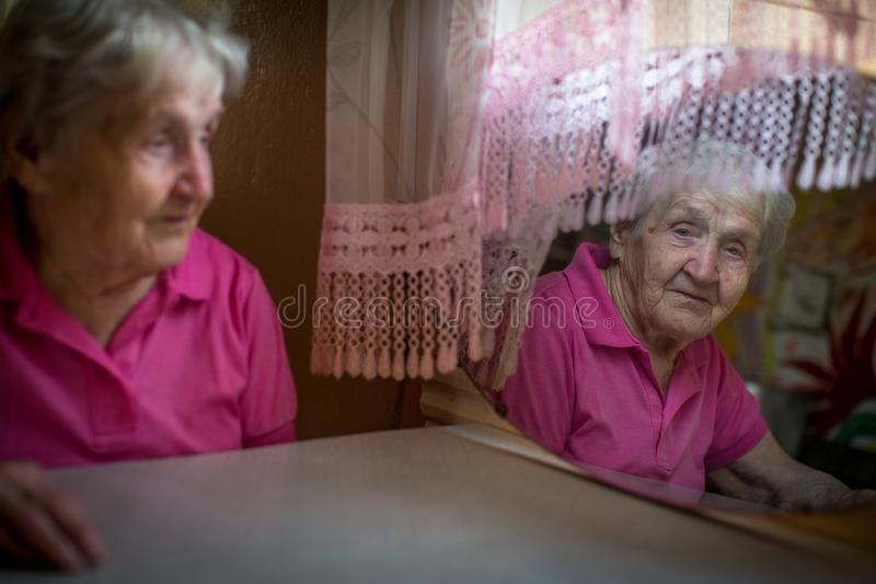 An elderly lone woman looks at her reflection in the mirror. stock images