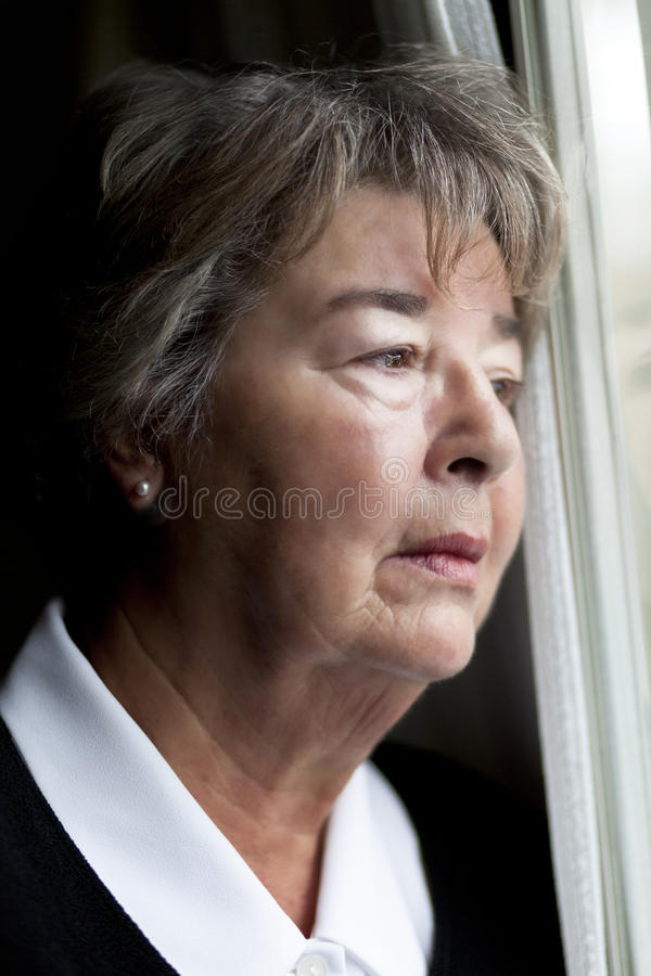 Elderly woman lost in thought royalty free stock photo