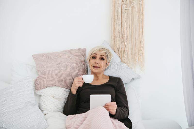 An elderly woman lying in bed drinking morning coffee uses a tablet to view news or chat with friends on a social. Network. Elderly generation and new stock images