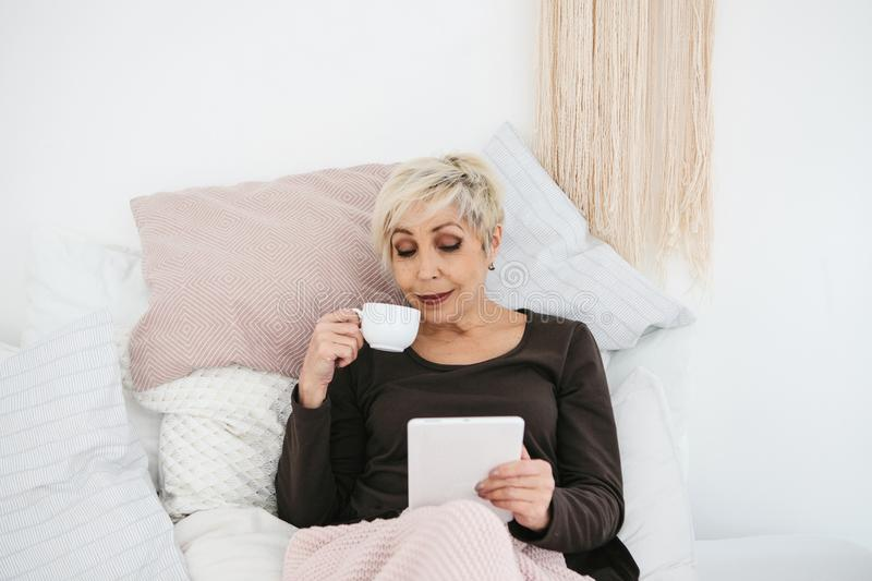 An elderly woman lying in bed drinking morning coffee uses a tablet to view news or chat with friends on a social. Network. Elderly generation and new stock photos