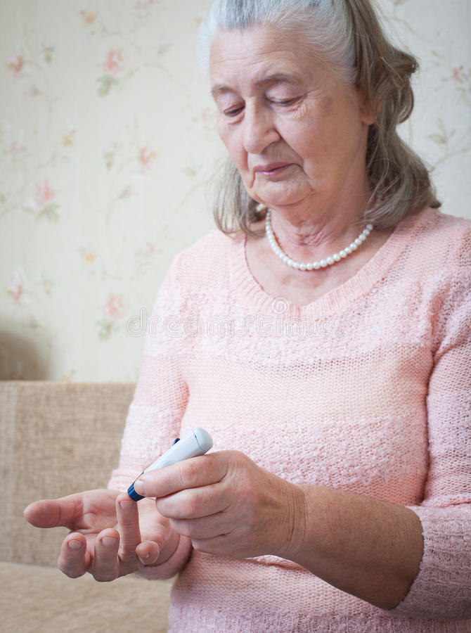 Elderly woman makes testing high blood sugar. Hands holding display glucometer closeup stock photo