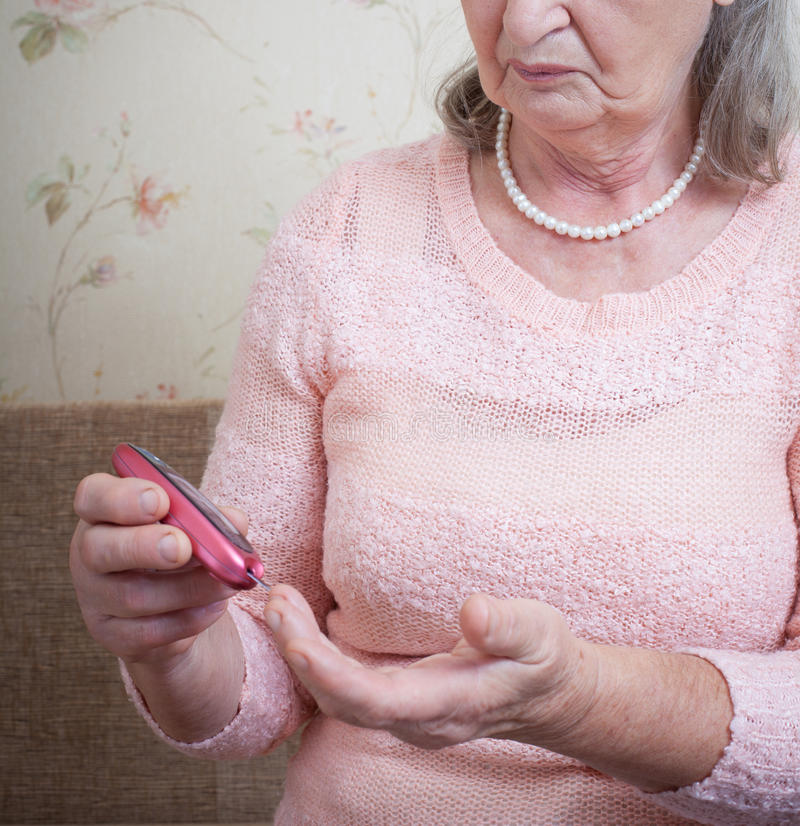 Elderly woman makes testing high blood sugar. Hands holding display glucometer closeup royalty free stock photography