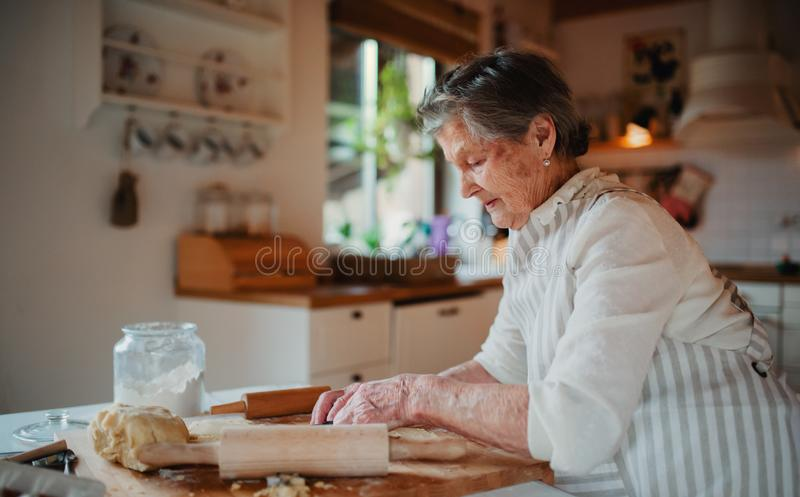 Elderly woman making cakes in a kitchen at home. Copy space. stock images