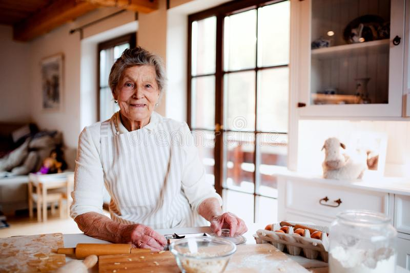 Elderly woman making cakes in a kitchen at home. Copy space. royalty free stock photo