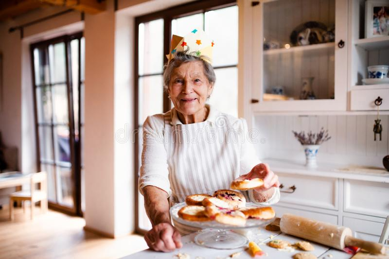Elderly woman making cakes in a kitchen at home. Copy space. stock photos