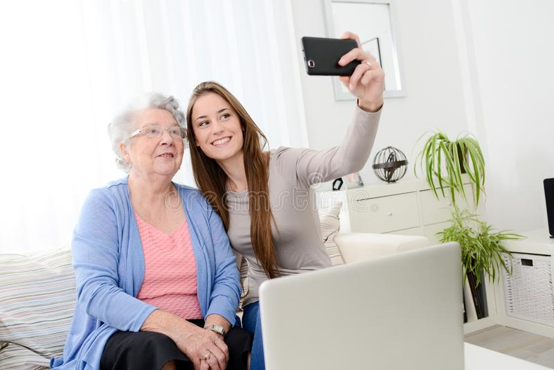 Elderly woman making selfie with her young granddaughter at home. Elderly women making a selfie with her young granddaughter at home royalty free stock images