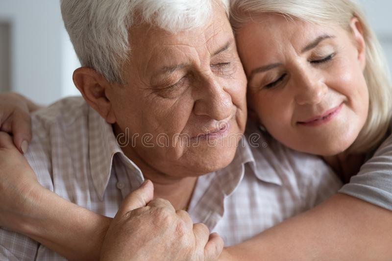 Elderly woman and man closed eyes embracing closeup view faces. Close up elderly men women embracing 70s husband and mature wife closed eyes feels calm peaceful royalty free stock images