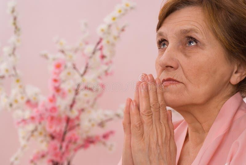 Elderly woman meditating stock photography