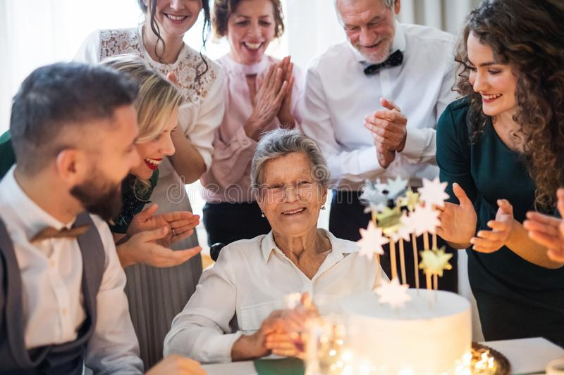 An elderly woman with multigeneration family celebrating birthday on indoor party. An elderly women with multigeneration family and a cake celebrating birthday stock images