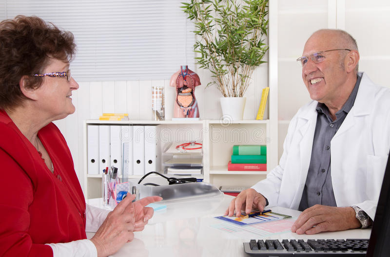 Elderly woman with older doctor talking together. Elderly women with older doctor talking together in his office royalty free stock photos
