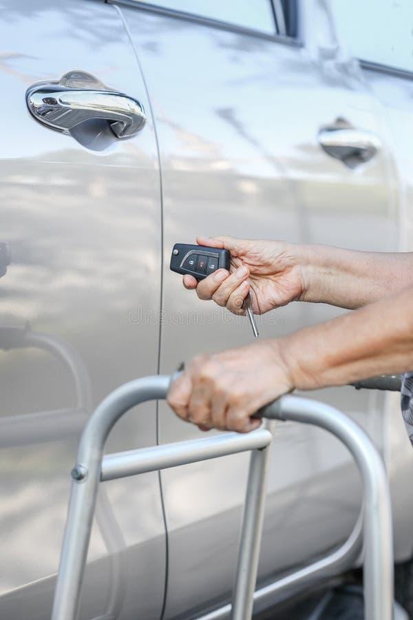 Elderly woman open the car on key car alarm. Elderly woman hand open the car on key car alarm systems royalty free stock photos