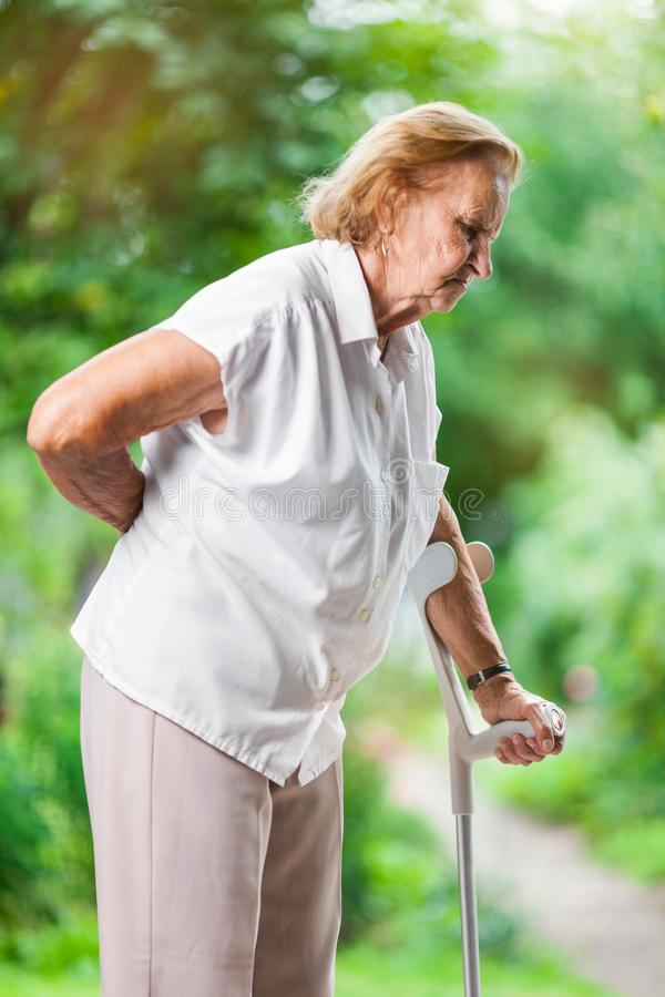 Elderly woman outdoors with back pain stock photo