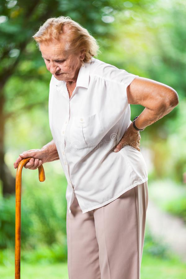 Elderly woman outdoors with back pain stock photography