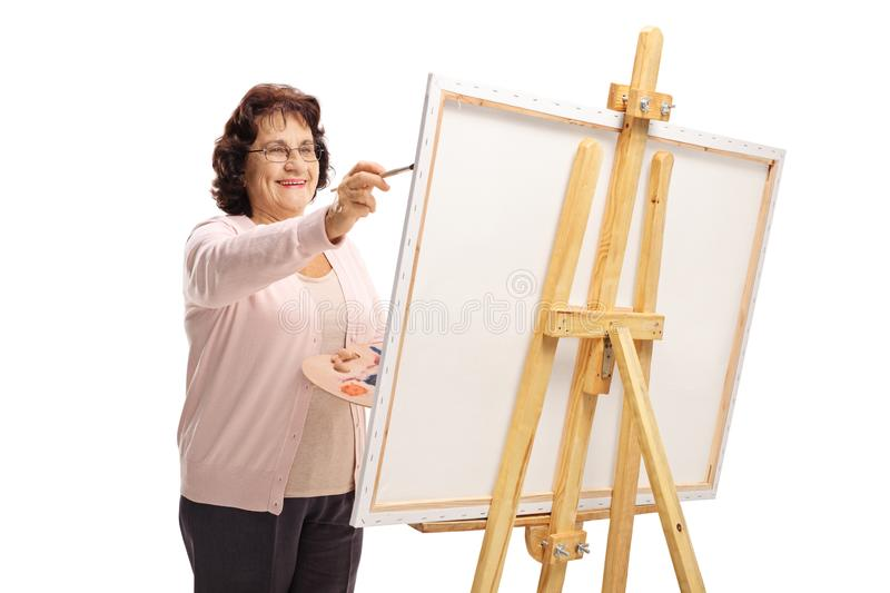 Elderly woman painting on a canvas. Isolated on white background royalty free stock photography