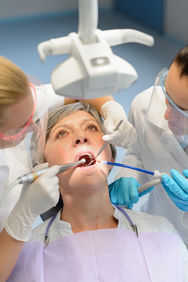 Elderly woman patient open mouth dental checkup. Elderly women patient open mouth dental checkup professional dentist team stock photography
