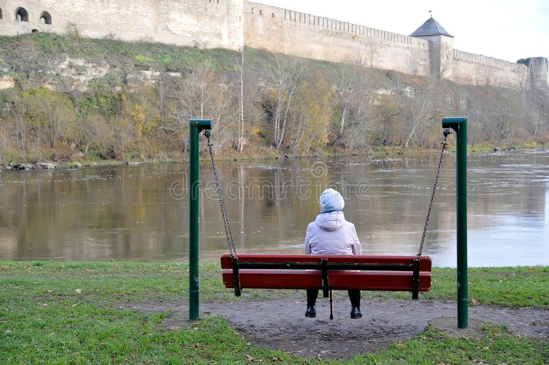 An elderly woman pensioner sitting on a bench and looking at the. River and the ancient fortress stock photography