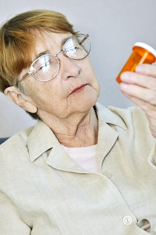 Elderly woman with pill bottle stock photo