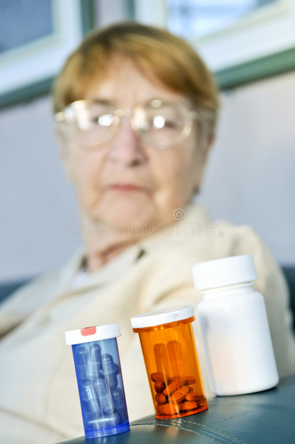 Elderly woman with pill bottles stock images