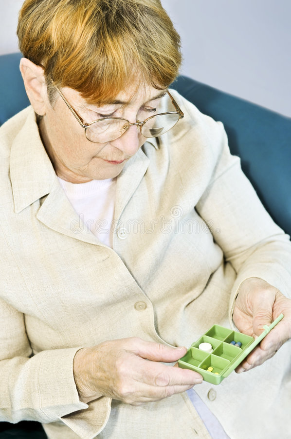 Elderly woman with pill box royalty free stock photo
