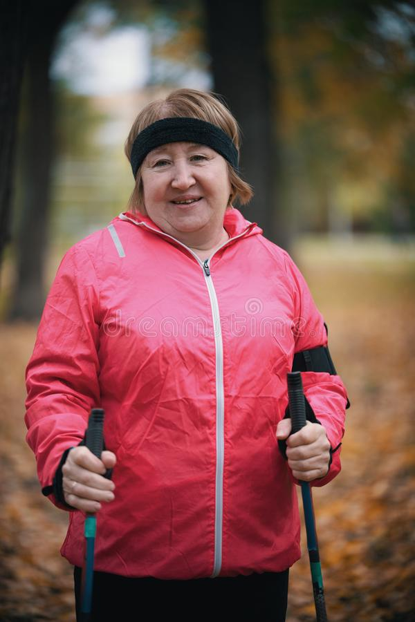 An elderly woman in a pink down jacket is standing in a park with sticks for nordic walking stock photography