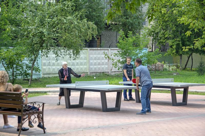 Elderly woman playing ping pong with her family.  royalty free stock images