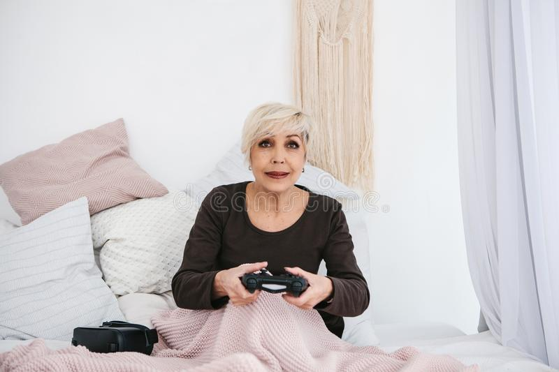 An elderly woman is playing a video game. Elderly person and modern technology. An elderly woman is playing a video game. Elderly person and modern technology royalty free stock photo