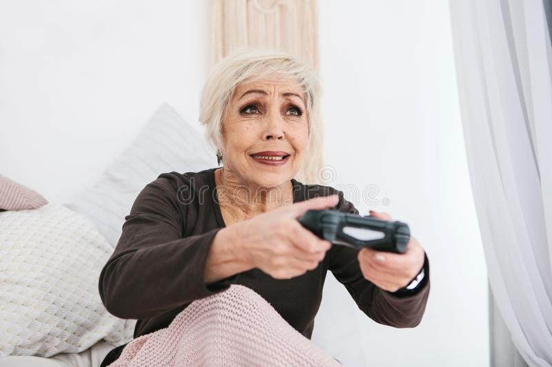 An elderly woman is playing a video game. Elderly person and modern technology. royalty free stock photos