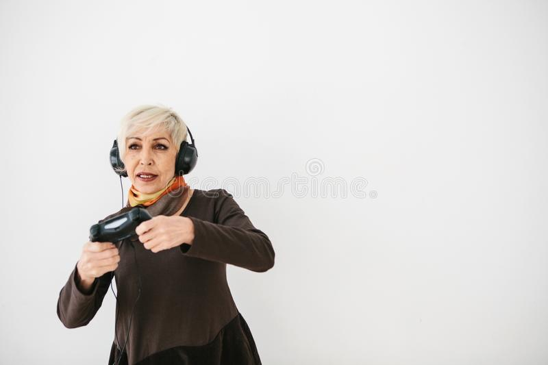 An elderly woman plays a video game and gestures that she won. Elderly person and modern technology. An elderly woman plays a video game and gestures that she stock photos