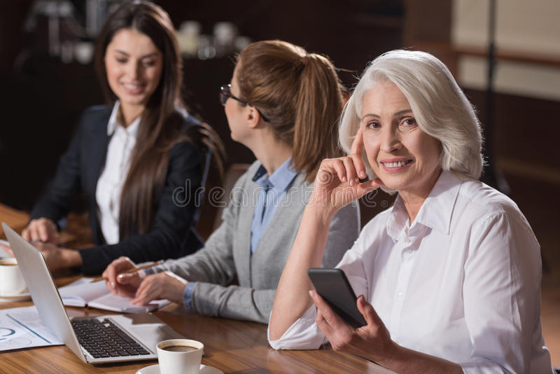 Elderly woman posing with her young colleagues. Different generations. Elderly elegant delighted women posing with her young colleagues while they working and stock photo