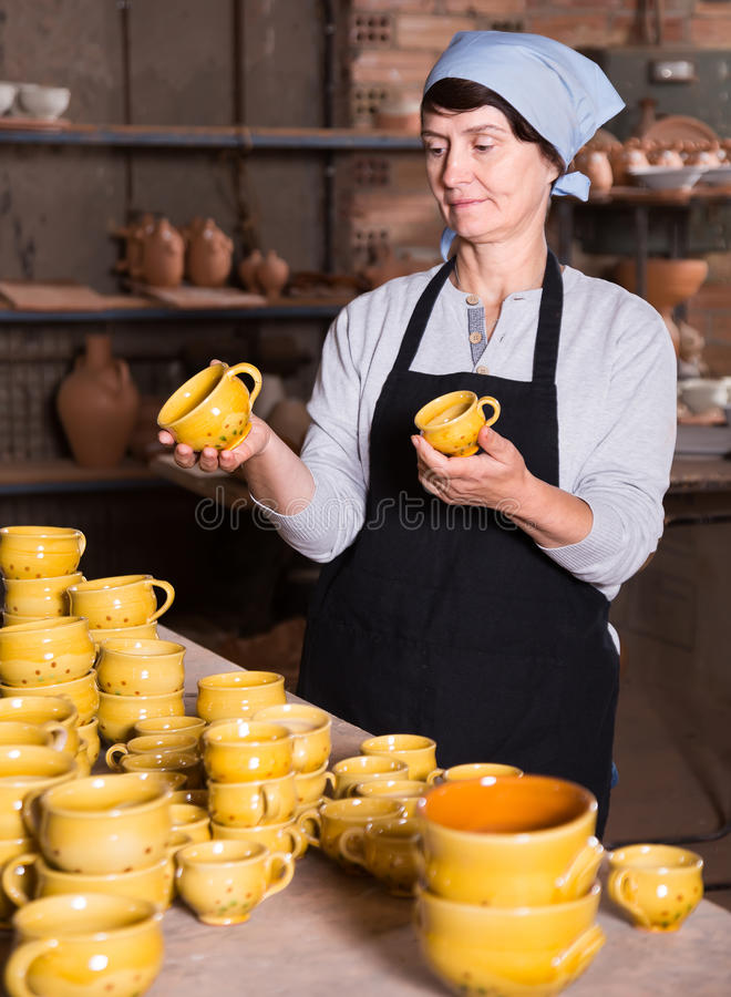 Elderly woman at pottery workshop. Portrait of positive senior woman holding ceramic cups at the workshop stock photography