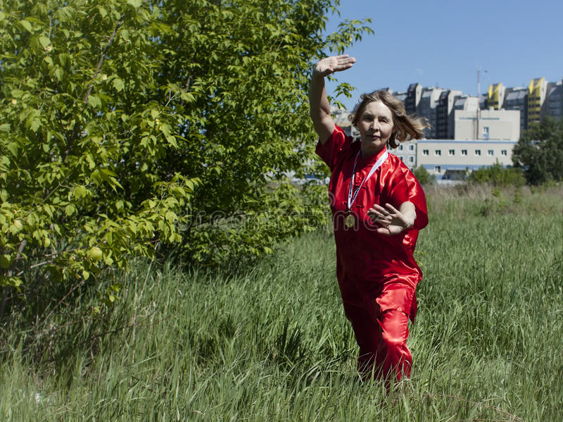 An elderly woman practicing Tai Chi. In the fresh air stock image