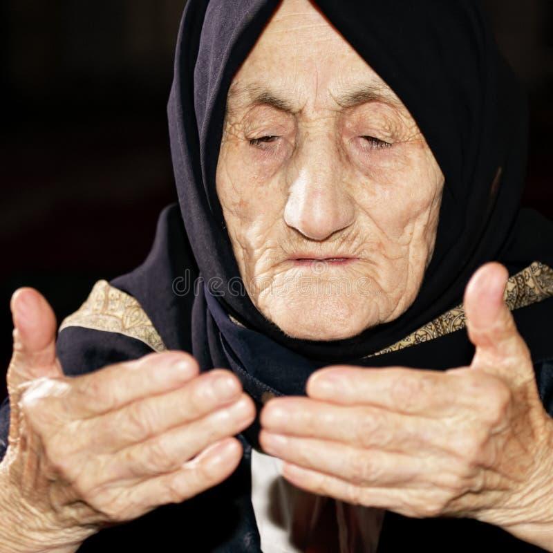 Elderly woman praying royalty free stock photos