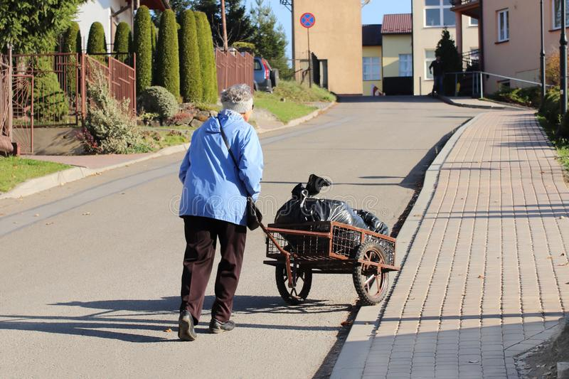 An elderly woman is pushing a wheelbarrow with a package of garbage in front of her. Removal of household waste. Ordinary life on royalty free stock photos
