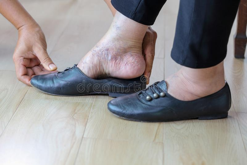 Elderly woman putting on shoes with care giver. Elderly woman putting on shoes with care giver at home royalty free stock photo