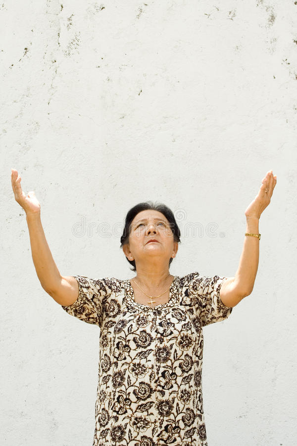 Elderly woman raising hands to worship stock image
